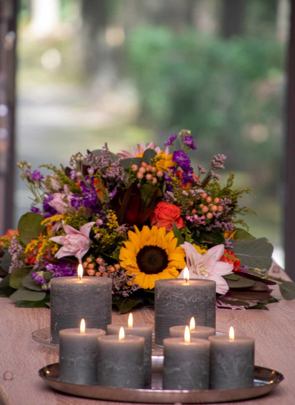 Een foto tijdens een uitvaart met bloemen, kaarsen en een kist